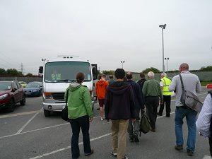 バスに乗り込む見学ツアーの参加者たち